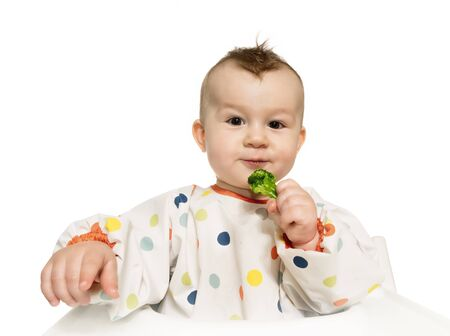 Portrait of funny baby boy that eats steamed broccoli on white isolated background.