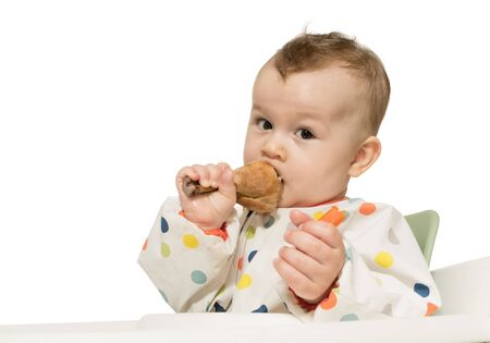Portrait of hungry baby boy with fried chicken leg in his hand on white isolated background.