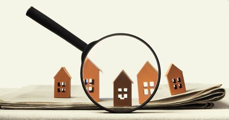 Magnifier in front of an open newspaper with paper houses. Concept of rent, search, purchase real estate. Banco de Imagens