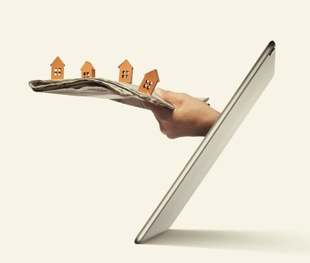 Newspaper with paper houses stick out of a tablet pc screen. Buying a house via internet. Concept of modern technologies in real estate industry.  Standard-Bild
