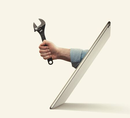 The human hand with  black wrench stick out of a digital tablet screen. Concept of technical support.