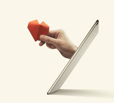 The woman hand with red paper heart stick out of a digital tablet screen. Concept of gift giving, donation, insurance and dating.