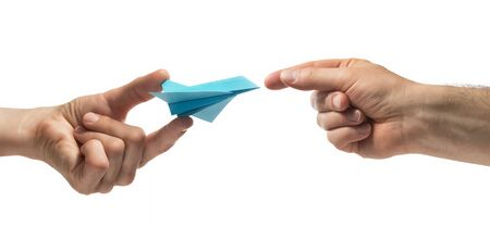 Person gives paper plane to another human. Concept of booking plane ticket, charters, tour. Isolated on white.