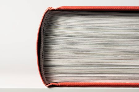 Closed book with red book cover. Close-up. Side view.