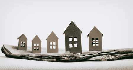 Open newspaper with paper houses. Concept of rent, search, purchase real estate.