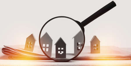 Magnifier in front of an open newspaper with paper houses. Concept of rent, search, purchase real estate.