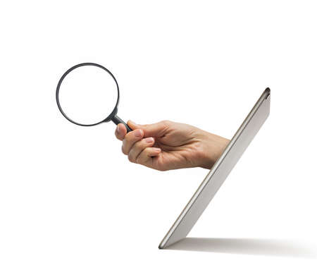 The human hand with magnifier stick out of a digital tablet screen on a white background.