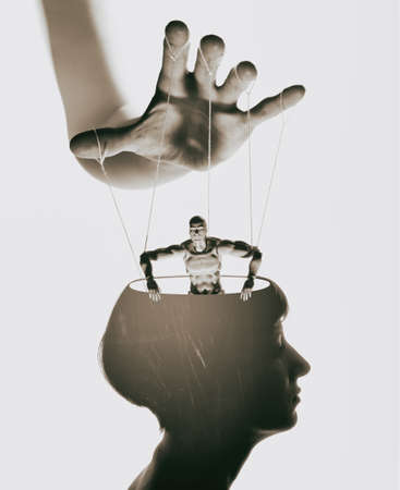 Marionette in human head. Concept of mind control. Image Stock Photo