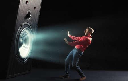 The sound wave from big sound speaker set back a screaming man in red shirt on black background. Image. Banque d'images