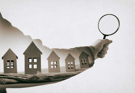 Hand with magnifier and paper houses on newspaper. Multiple exposure. Concept of real estate. Black and white. Stock Photo