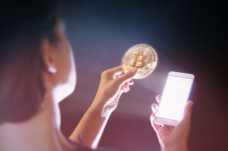 A woman is holding a virtual bitcoin from her smartphone. Bitcoin transactions. Concept