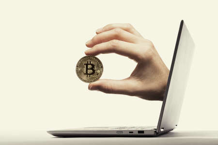 The woman hand with virtual bitcoin stick out of a laptop screen. Bitcoin transactions. Concept