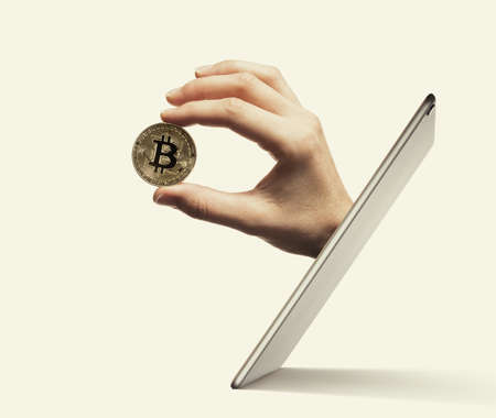 The woman hand with virtual bitcoin stick out of a digital tablet screen. Bitcoin transactions. Concept