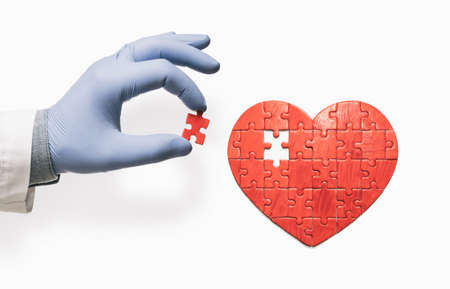 Heart-shaped puzzle and doctor's hand with the missing piece of puzzle. Heart treatment concept. Reklamní fotografie
