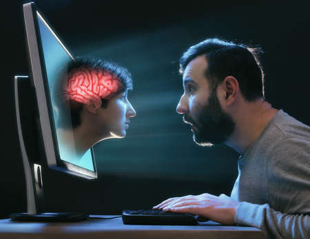 A woman's head as a metaphor for artificial intelligence peeks out of a laptop screen. Reklamní fotografie