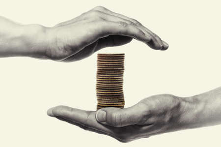 Stack of coin are protected by woman hands. Black and white. Concept safe custody of cash.