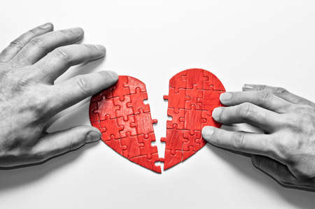 Two people break up a heart-shaped puzzle. Damaged relationships concept.