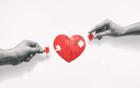 Two people put together a heart-shaped puzzle. The concept of building love relationships.