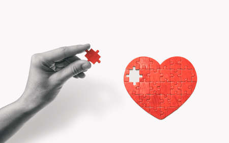 Heart-shaped puzzle and human hand with the missing piece of puzzle. Love relationships concept. Reklamní fotografie