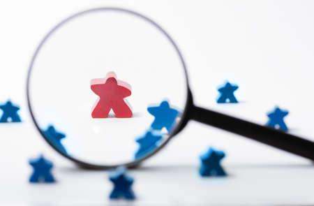 A toy red wooden figure of human under magnifying lens. Business recruitment, talent management. Reklamní fotografie