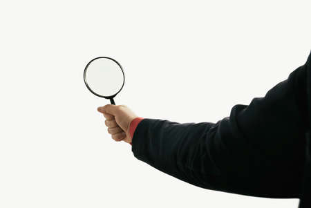 Magnifying glass in man hand on isolated toned background.