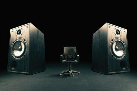 Two sound speakers with office chair between them on black background. Banco de Imagens