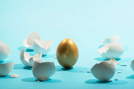 Intact golden egg among broken white eggs. The concept of reliability, resistance to adverse conditions.
