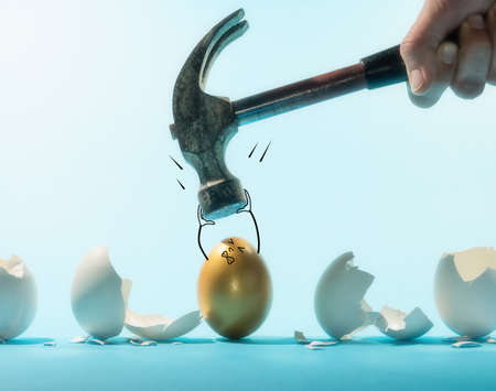 Intact golden egg holds the hammer among broken white eggs. Funny character. The concept of reliability, resistance to adverse conditions.