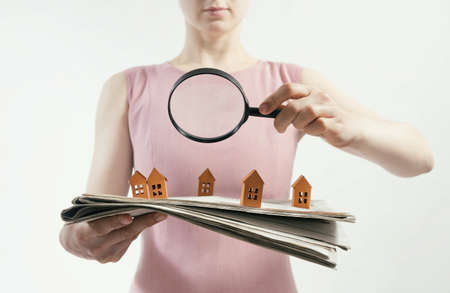 The woman with magnifier holds a newspaper with paper houses in front of yourself. Concept of real estate, housing development.