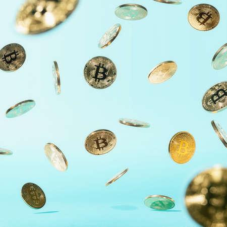 Falling bitcoin coins on blue background. Rain of bitcoin. Bitcoin background. Abstract.
