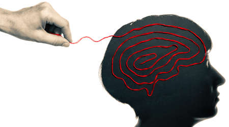 The woman hand pulls on the thread laid out in the shape of a brain in woman head. Solving mental health problems. Standard-Bild