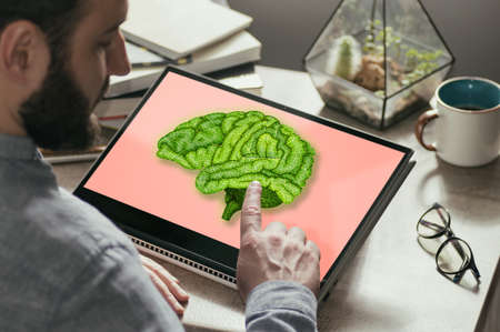 A man touches a brain on a laptop screen. Online consultation, medical test results. Solving mental health problems.