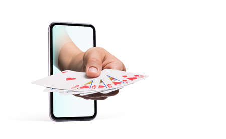 Hand sticks out of the smartphone screen and holds cards. Concept of online casino.
