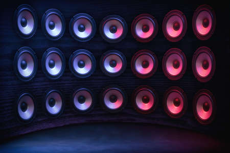 Group of sound speakers in neon light on black. Stock Photo