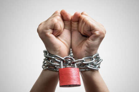 Human hands are linked by a chain with a red padlock. Trafficking, slavery, domestic violence. Concept