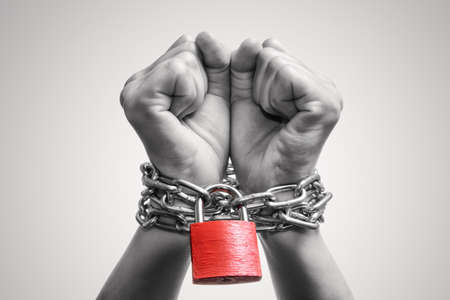 Human hands are linked by a chain with a red padlock. Black and white. Trafficking, slavery, domestic violence. Concept Stock Photo
