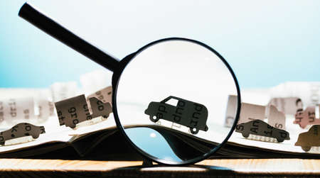 Open newspaper with paper cars and magnifier. Concept of car rental, search, purchase and cargo transportation.