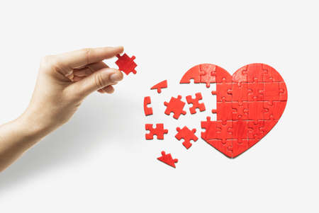 Heart-shaped puzzle and human hand with the missing piece of puzzle. Love relationships concept. Stock Photo