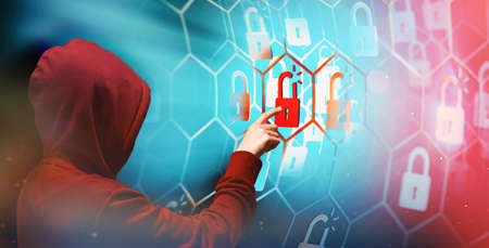 Person in a hoodie is hacking computer networks security.