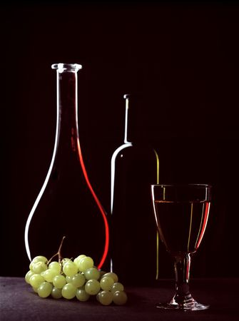 Bottles with wine, a glass and grapes cluster