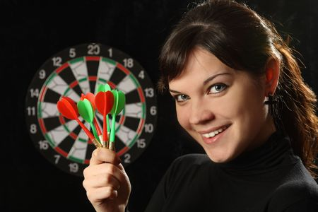 The beautiful girl with darts on a black background