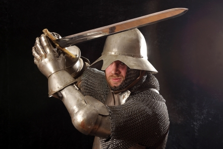 Le soldat dans une armure de chevalier médiéval nous jeter dans les mains Banque d'images - 4739036