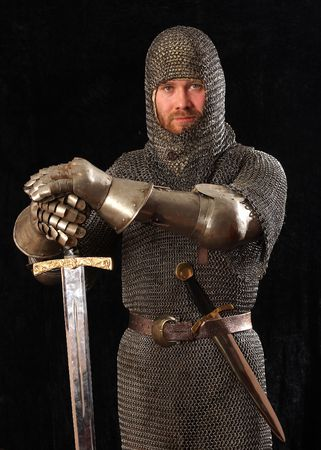 The soldier in a medieval knightly armour with we throw in hands Stock Photo - 4739044