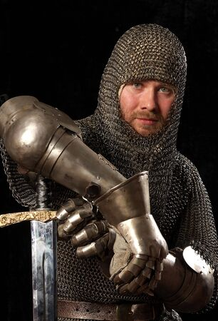 vestidos de epoca: El soldado en una armadura medieval caballeresca con que tirar en las manos
