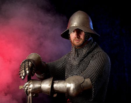 The soldier in a medieval knightly armour with we throw in hands Stock Photo