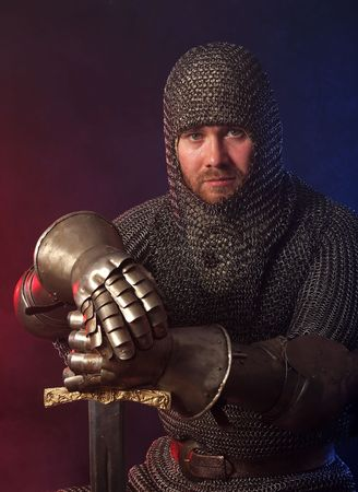 The soldier in a medieval knightly armour with we throw in hands photo