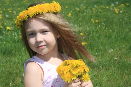 The little girl on a meadow with a bouquet of dandelions photo
