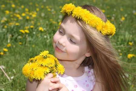 The little girl on a meadow with a bouquet of dandelions