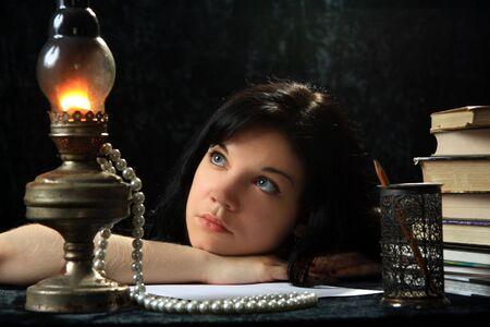The beautiful girl longs, looking at an oil lamp  photo