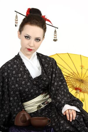 The Japanese geisha on a white background with a fan and an umbrella Stock Photo - 5146567